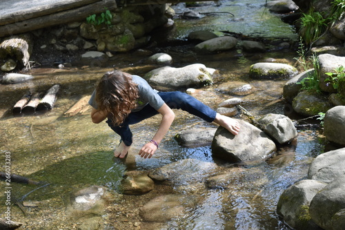 Fotomural Barefoot boy exploring stream or creek