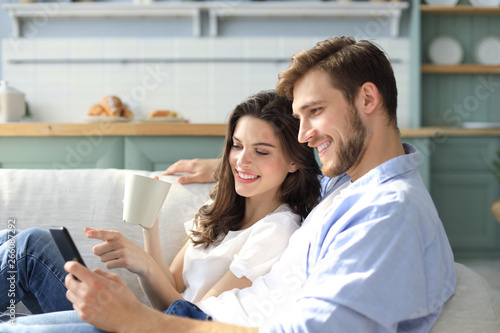 Young couple watching online content in a smart phone sitting on a sofa at home in the living room.