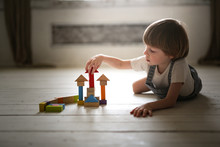 Boy Playing Wooden Constructor On Floor At Home