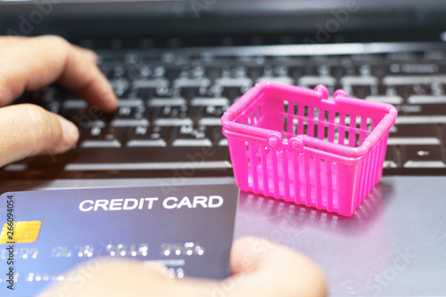 Photo Basket shopping and hand holding mock up of credit card on laptop keyboard