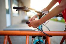 Girl Teenager Fastening Bicycle Lock On Street Parking At Sunset