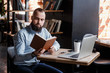 Young successful bearded businessman, working at a laptop, muzhschina looks at his notes in blaknote in a cozy loft foise Coworking