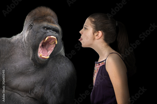 Brave young girl defying an angry gorilla Tablou Canvas