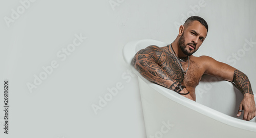 Foto op Aluminium Ontspanning spa and hygiene. time to relax in bathroom. confidence charisma. brutal sportsman. steroids. muscular man with athletic body. sexy abs of tattoo man in bath tub. stay clean and fresh. copy space
