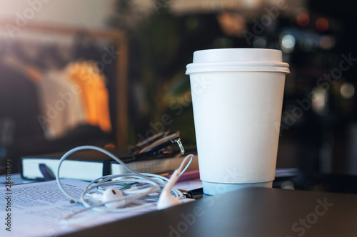 Aluminium Prints Equestrian Closeup of a white paper cup of coffee on a table in an empty cafe without people. Nearby are the headphones and notebook. Mockup.