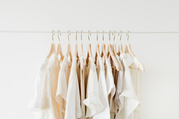 Minimal fashion clothes concept. White female blouses and t-shirts on hanger on white background.