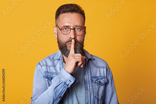 Fotografija  Serious middle aged emotionless bearded man in blue shirt, showing silence gesture, asks to keep secret, putting forefinger on lips, male dressed in denim jacket stands over pink background