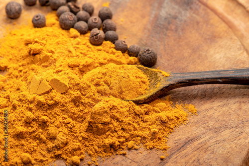 Indian Turmeric or Curcuma with Pepper and Spoon on wooden Table