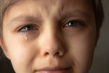 Tears In The Eyes Of A Child. A Tear On The Boy's Cheek.