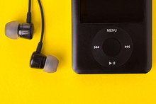 Music Player And Headphones On A Yellow Background. Black Headphones And Player Close-up.