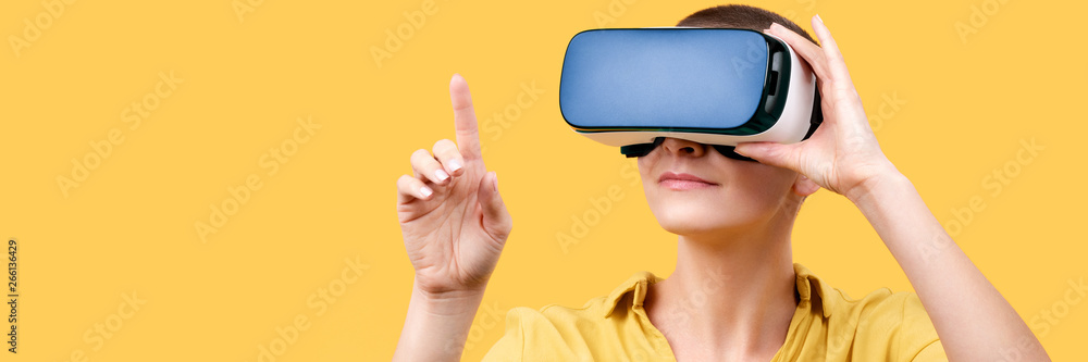 Fototapeta Young woman in her 30s using virtual reality goggles. Woman wearing VR headset isolated over yellow banner. VR experience concept.