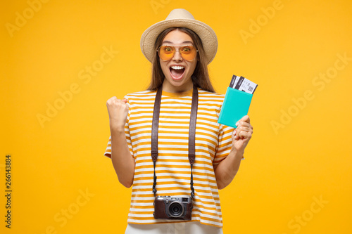 Fotografering  Young female tourist standing with flight tickets screaming if she is a winner,