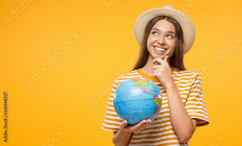 Young female dreaming about future trip, holding globe with one hand, isolated on yellow background Fototapet