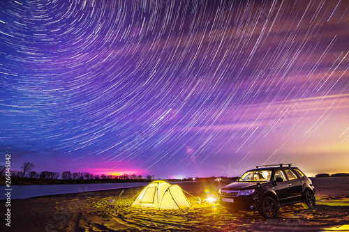 Poster Prune Night camping at the river. Star trails in the sky.