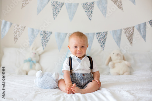 Photo  Cute toddler child, baby boy, playing with colorful toy in sunny bedroom