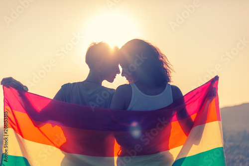 Beautiful lesbian couple with rainbow flag Wallpaper Mural