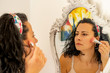 Beautiful woman applying blusher ( make up ) to her face at a mirror reflection