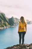Woman traveling in Norway summer vacations tourist standing alone on mountain cliff over sea active lifestyle adventure trip outdoor