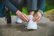 woman tie shoelaces on sneakers