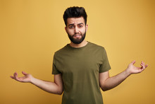 Unsure Doubtful Bearded Man Wearing Green T-shirt Shrugging His Shoulders In Questioning Gesture Of Uncertainty. Close Up Photo. Issolated Green Background