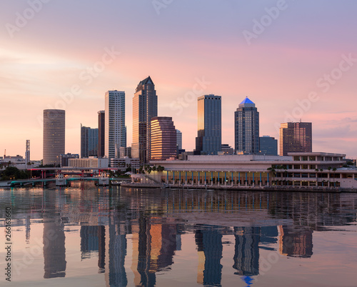 Florida skyline at Tampa with the Convention Center on the riverbank. Sun is just setting at dusk giving a fiery glow to the night sky.