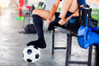 Soccer player is sitting and putting black sport sock with soccer ball