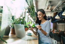 Beautiful Smiling Young Woman Using Laptop And Doing Shopping Online With Help Of Her Smartphone And Card