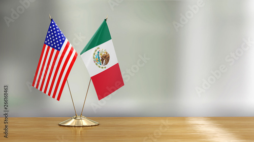 Fotografía  American and Mexican flag pair on a desk over defocused background
