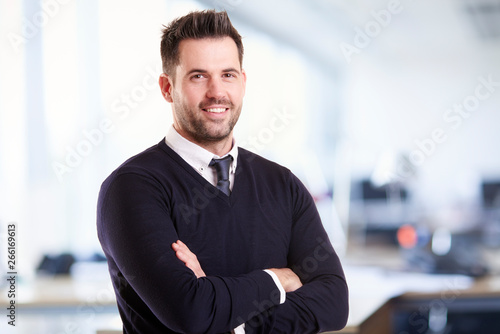 Businessman standing with folded arms in the office