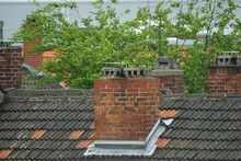 Rooftops With Brick Chimneys A...
