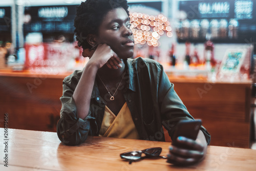 Foto  A thoughtful young African woman with short afro hair is pensively looking aside