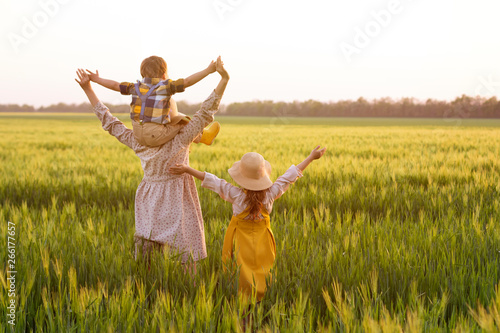 Photo  Happy family, mom, son and girl in straw hat in wheat field at sunset