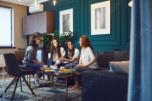 Papiers peints Individuel Young women having tea party at home