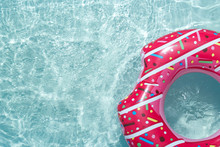 Inflatable Float Rubber Ring In The Form Of A Pink Donut In The Blue Water Of The Pool.