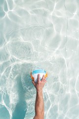 water polo player with a ball in a blue pool water. Top view. Copy space.