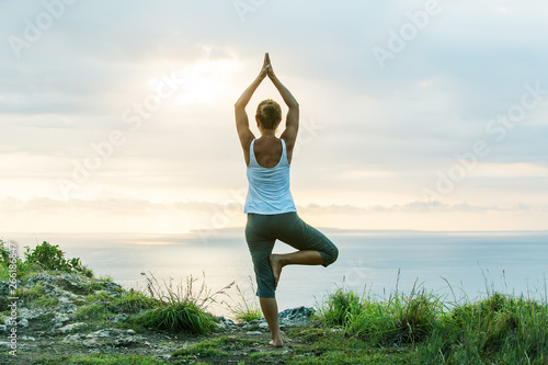 In de dag School de yoga Caucasian woman practicing yoga at seashore