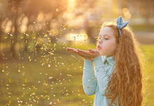 Little Girl Blowing Gold Confe...