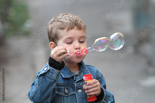 The boy in the denim jacket blows bubbles Canvas Print
