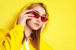Leinwandbild Motiv Pretty young girl with red glasses, and yellow hood on.
