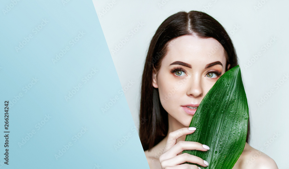 Fototapety, obrazy: Portrait of young beautiful woman with healthy glow perfect smooth skin holds green tropical leaf, look into the hole of colored blue paper. Model with natural nude make up.