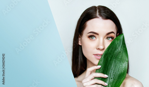 Portrait of young beautiful woman with healthy glow perfect smooth skin holds green tropical leaf, look into the hole of colored blue paper. Model with natural nude make up.