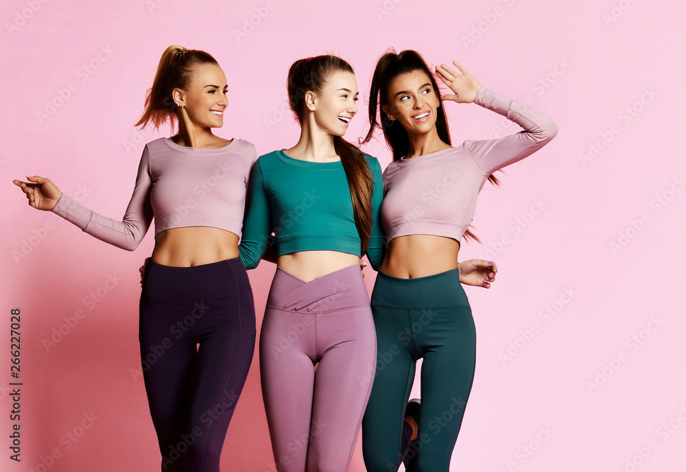 Fototapety, obrazy: Fitness sport girls friends in blue, grey, brown walk together, talk and laugh. Girls in good shape on pink background