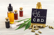 canvas print picture - Full spectrum Cannabidiol CBD oils, capsules and crystals isolate with small blackboard with CBD word and chemical structure