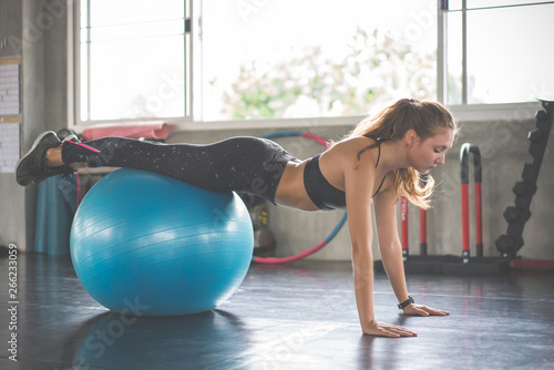 Photo  Young beautiful woman training pilates exercises with fit ball in fitness gym