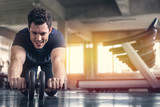 Athlete sporty man doing exercise with abs roller wheel to strengthen his abdominal muscle in gym