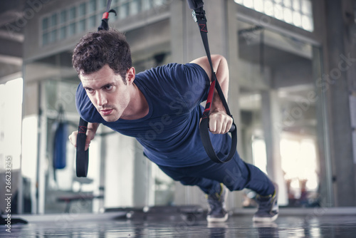 Athlete sporty man doing exercise with fitness trx straps to strengthen his abdo Canvas Print