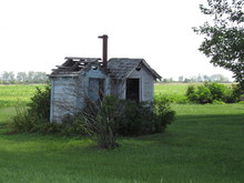 Old Outhouses In A Field