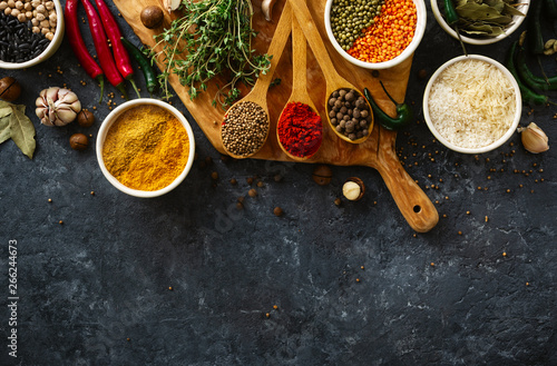 Spices, herbs, rice and various beans and seasonings for cooking on dark backgraund with copy space top view