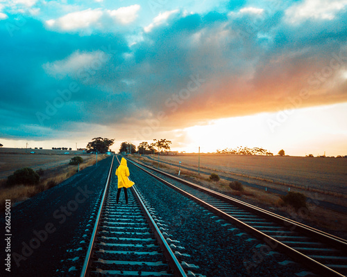Person in Yellow Jacket on Old Train Tracks With Epic Sky