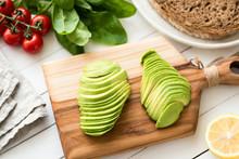 Sliced Avocado On Wooden Cutti...